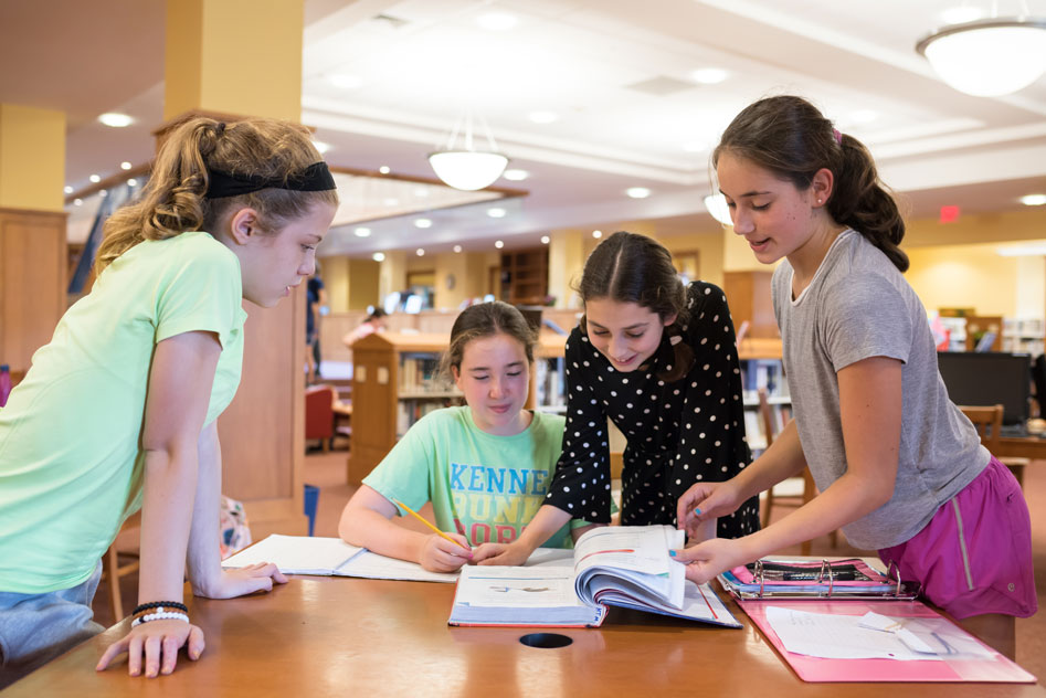 Girls gathered around table in library