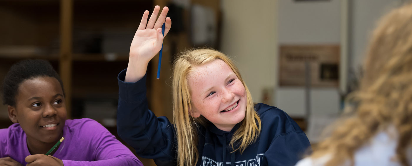 middle school student with hand raised