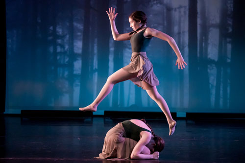 Girl leaping over another dance student with a forest as the backdrop