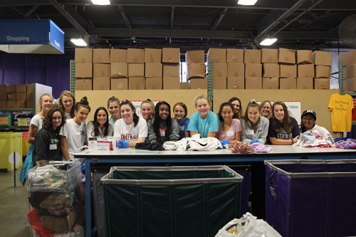 Girls volunteering at cradles to crayons sorting clothes