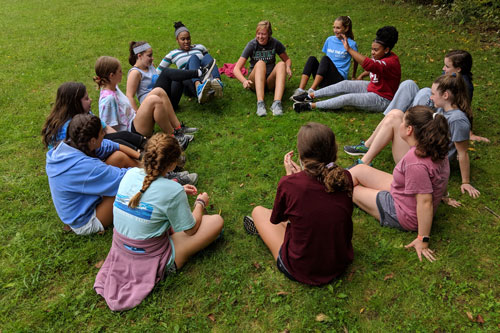 girls sit in an circle and play a game during their retreat